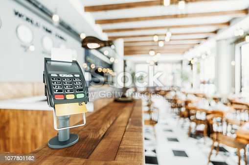 Close-up shot of a counter-top payment terminal in an empty restaurant.
