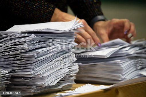 a pair of hands counting piles of ballot papers during an election