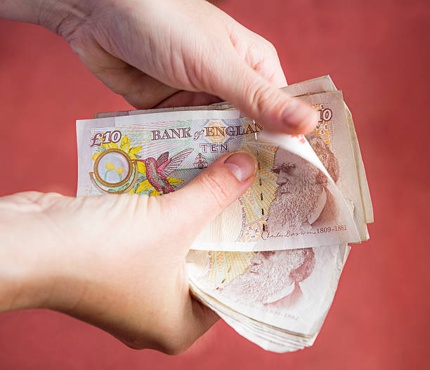 Counting British Money Counting ten pound notes. ten pound note stock pictures, royalty-free photos & images
