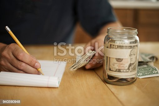 A male writes notes concerning money at the kitchen table.  On the table is a pencil, pad of paper, paper currency and a jar fill with cash and coins.  The jar as blank masking tape to hold text.