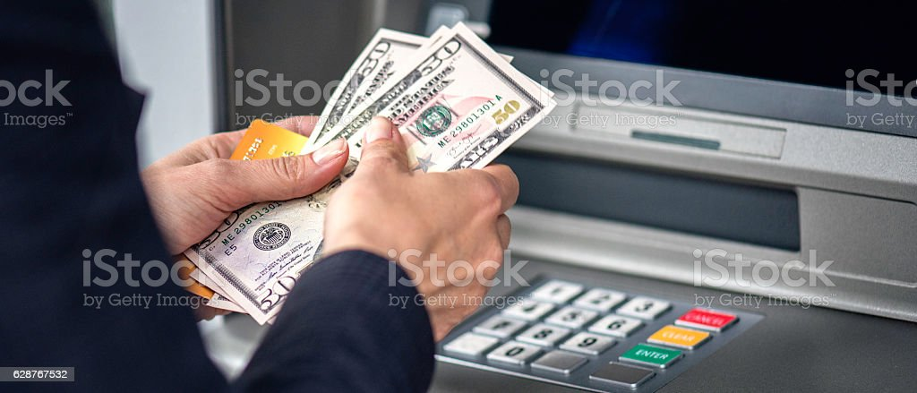 Counting dollars from ATM machine stock photo