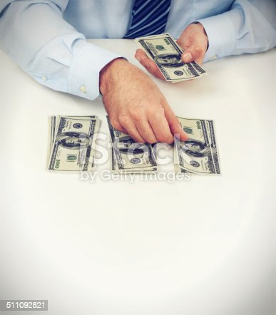 Cropped shot of a male counting American money