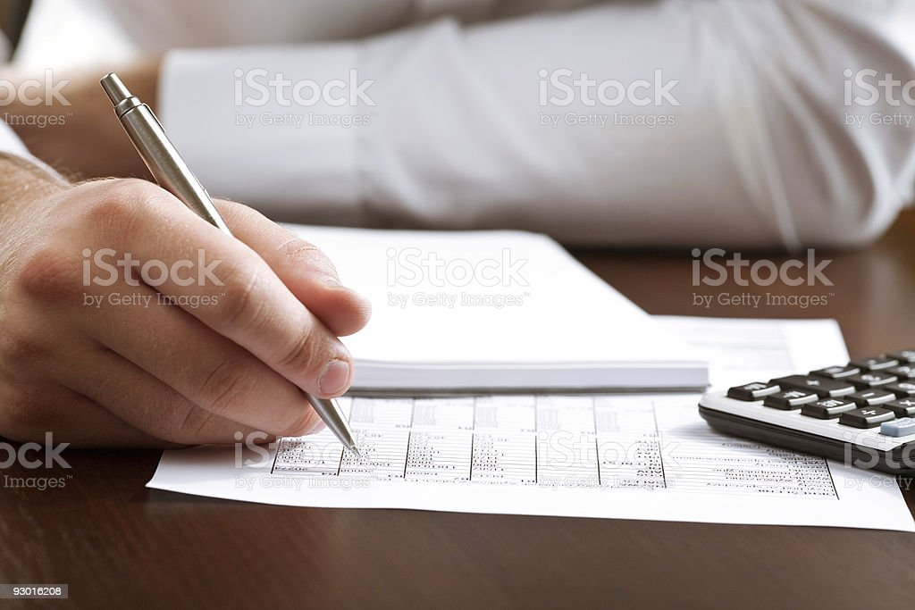 Counting income on calculator royalty-free stock photo