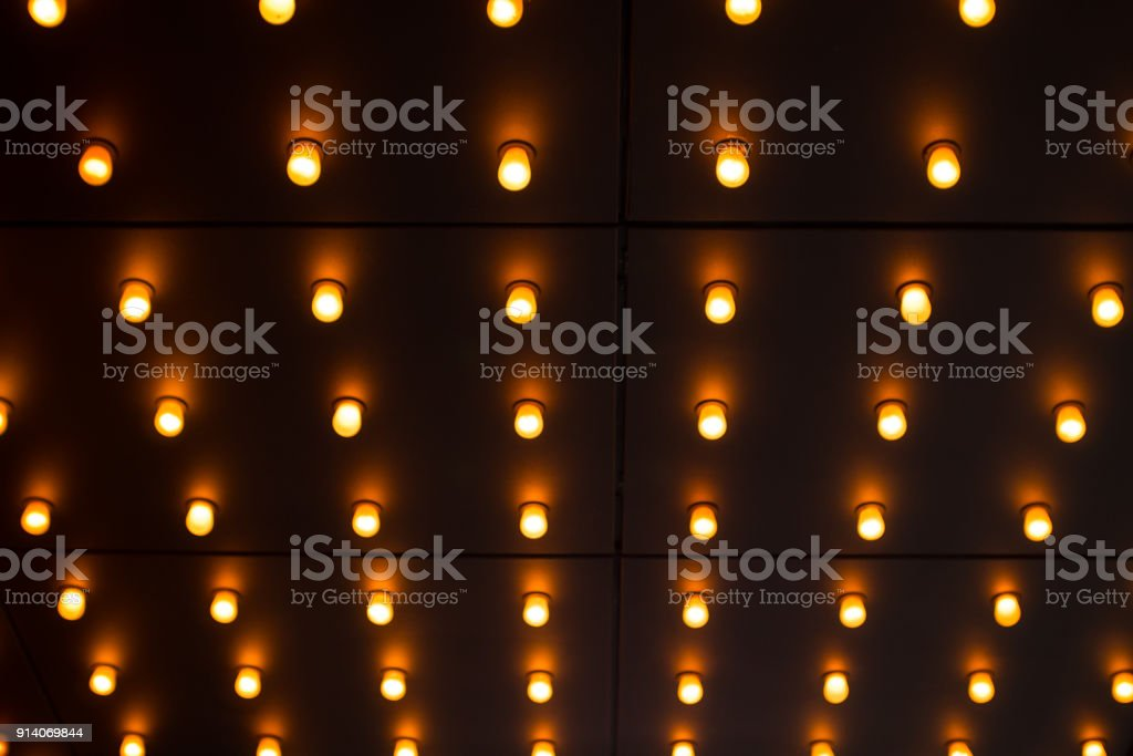 Countless glowing lightbulbs on ceiling stock photo
