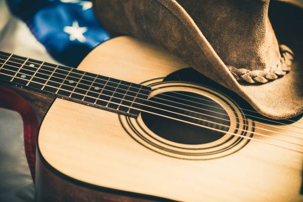 Country and western music. Acoustic Guitar and Cowboy Hat with American Flag on Background country and western music stock pictures, royalty-free photos & images