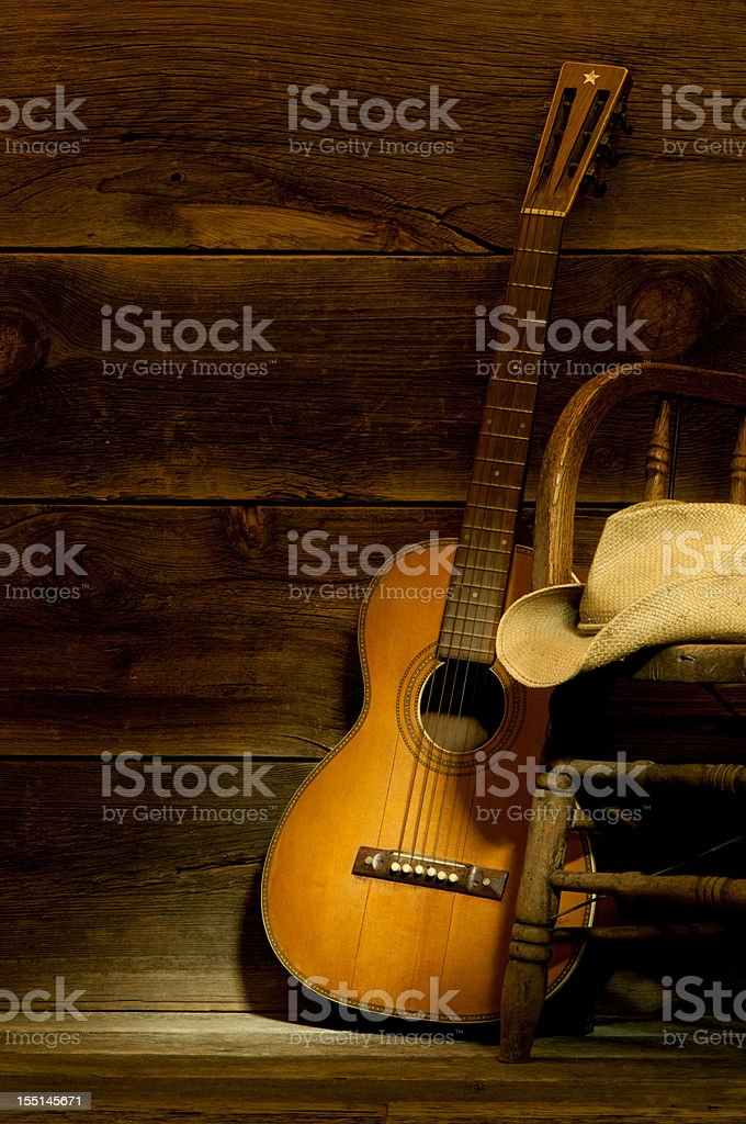 Country and Western scene w/ guitar,chair,cowboy hat-barnwood background stock photo