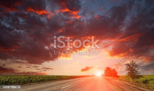 1155573645istockphoto Country asphalt road leaving on dramatic bright sunset sky 1026786410