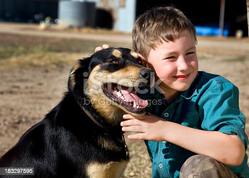Little farmer on the land with his Kelpie sheep dog.