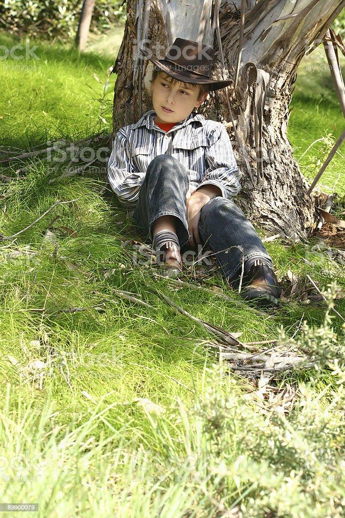 Land junge sitzt unter einer gum tree Lizenzfreies stock-foto