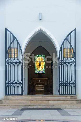 istock Country church door welcome open showing Silhouette jesus christ on cross inside. 1210795554