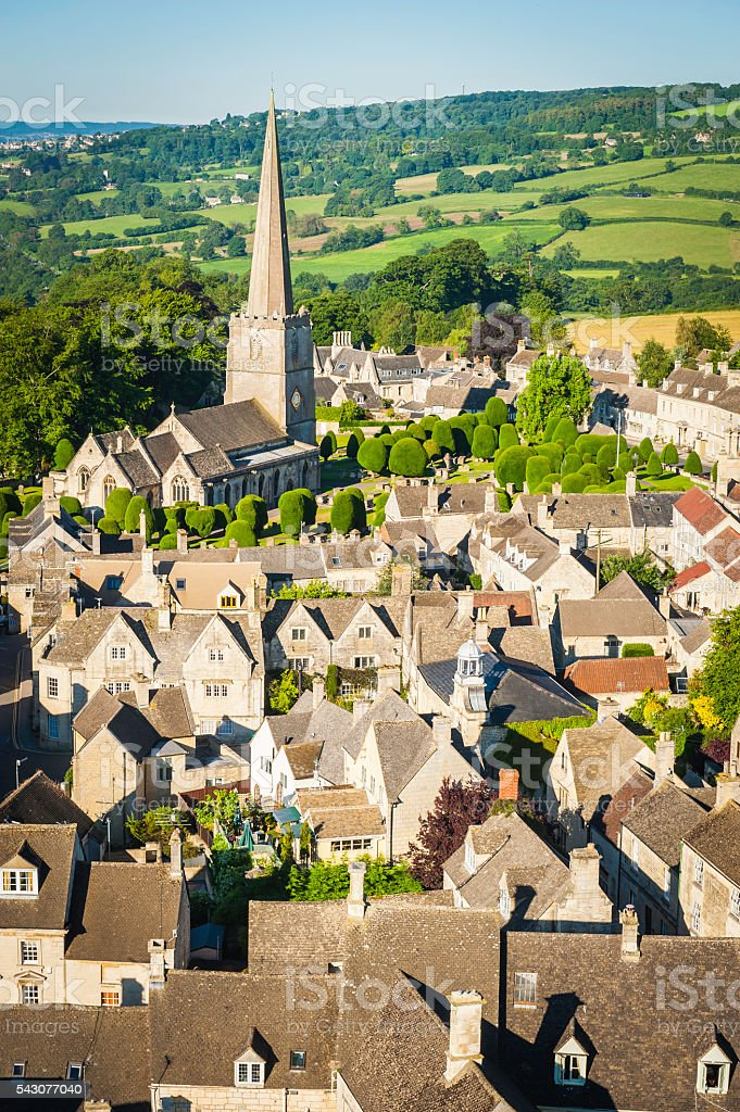 Country church spire overlooking pretty village cottages farms Cotswolds UK stock photo
