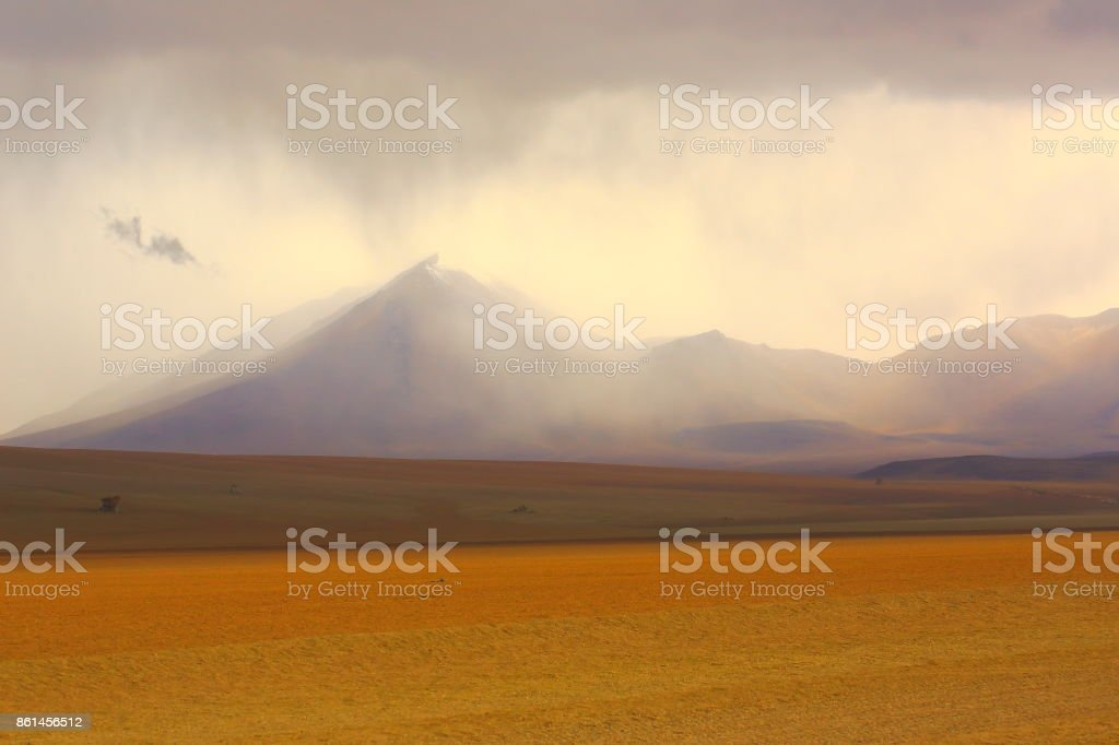 Country dirt road – Stormy weather and storm clouds to Impressive Bolivian Andes altiplano barren steppe and Idyllic Atacama Desert, Volcanic landscape panorama – Potosi region, Bolivian Andes, Chile, Bolívia and Argentina border stock photo