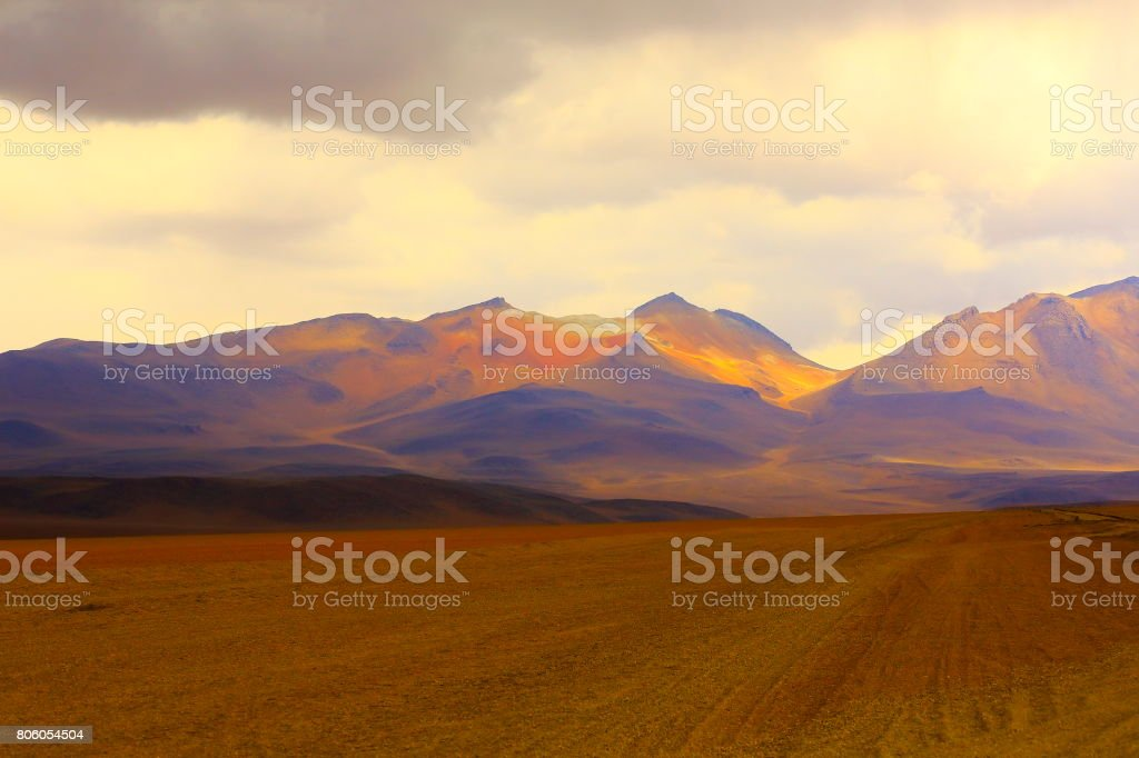 Country dirt road to Impressive Bolivian Andes altiplano and Idyllic Atacama Desert, Volcanic landscape panorama – Potosi region, Bolivian Andes, Chile, Bolívia and Argentina border stock photo