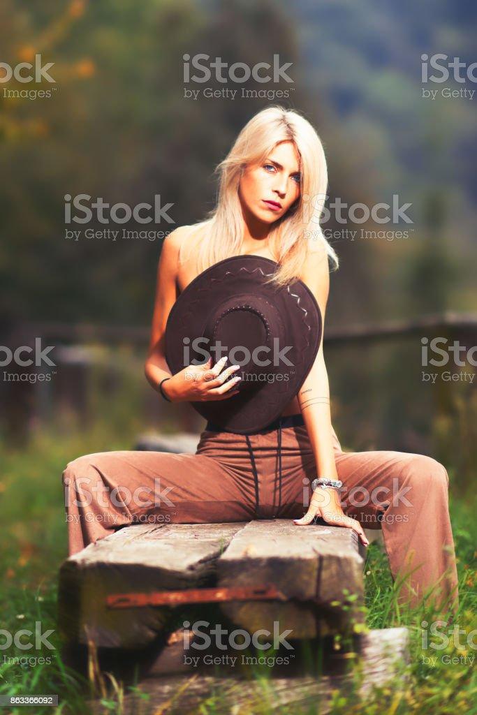 Photo Libre De Droit De Fille De La Campagne Portant Sur Sa Poitrine Avec Un Chapeau De Cowboy Et Assis Sur Un Banc En Bois Portrait En Plein Air Avec Un Guide