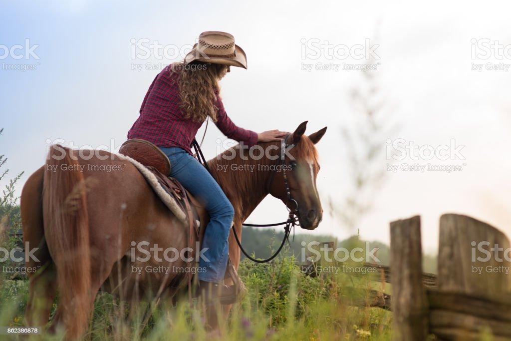 Country Girl Early Morning Ride Back View stock photo