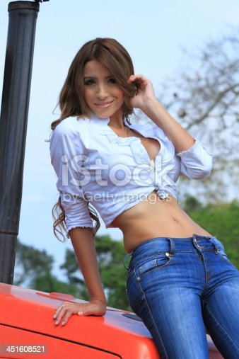 Young sexy beautiful country lady posing at a tractor in a farm