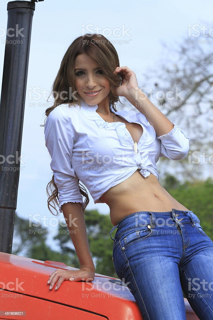 Country Girl Posing at Tractor stock photo