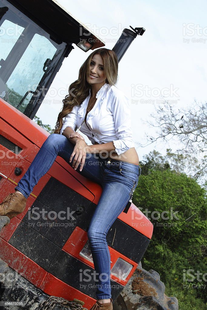 Country Girl Sitting on Tractor stock photo