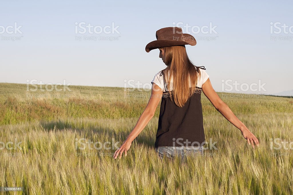 Country Girl Walking in Golden Grain Field royalty-free stock photo