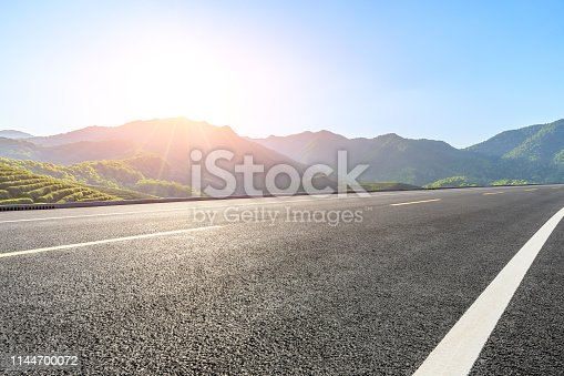 Empty country highway and green mountains natural landscape