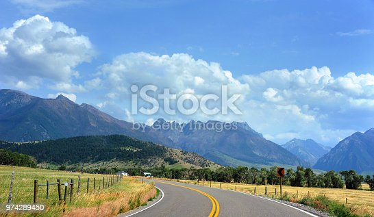 Country highway curves toward the beautiful Absaroka Mountains in Paradise Valley, Montana.