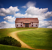 'Camera: CanonLens: 24-85mmLocation: Surrey, U.K.A composite image of a large barn styled house on a green hill, with a winding front path, set against a blue summer sky.'
