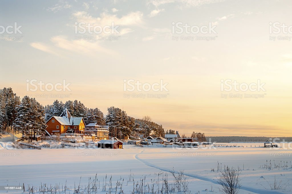 Country house on lake shore in winter sunset lights stock photo