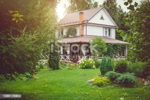 Country cottage with green landscaped back yard in sunny summer day