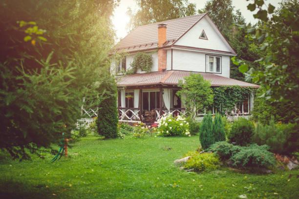 güneşli yaz gününde yeşil arka yard ile kır evi - kır evi stok fotoğraflar ve resimler