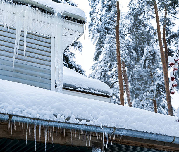 Country house with icicles Corner of country house with icicles on roof in winter. Pine trees in background russian dacha stock pictures, royalty-free photos & images