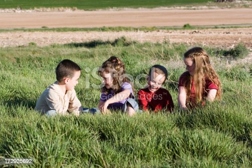 Four cute kids playing in tall grass.