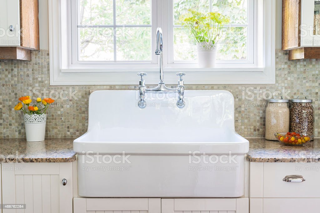 Country Kitchen Counter With Tile Backsplash And Deep Sink Stock