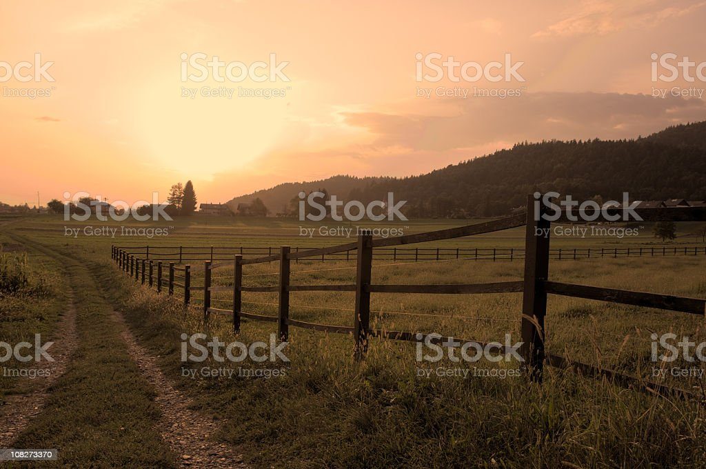Country landscape with pasture and fence at dusk royalty-free stock photo