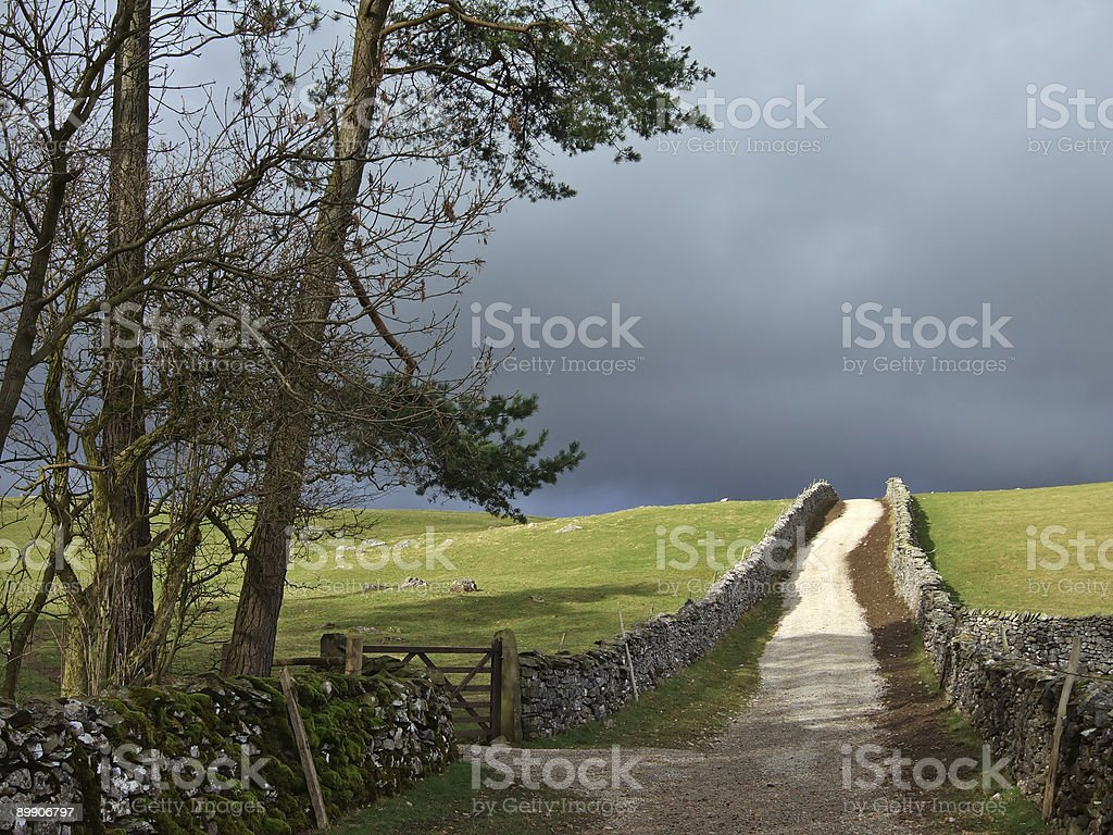 Country lane in the Yorkshire Dales under a stormy sky royalty-free stock photo