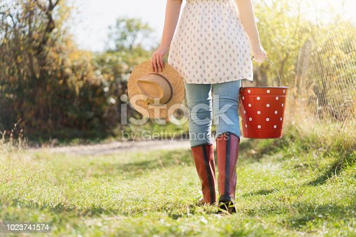 Rear view of an unrecognizable female farmer carrying a metal bucket and a hat through the country yard.