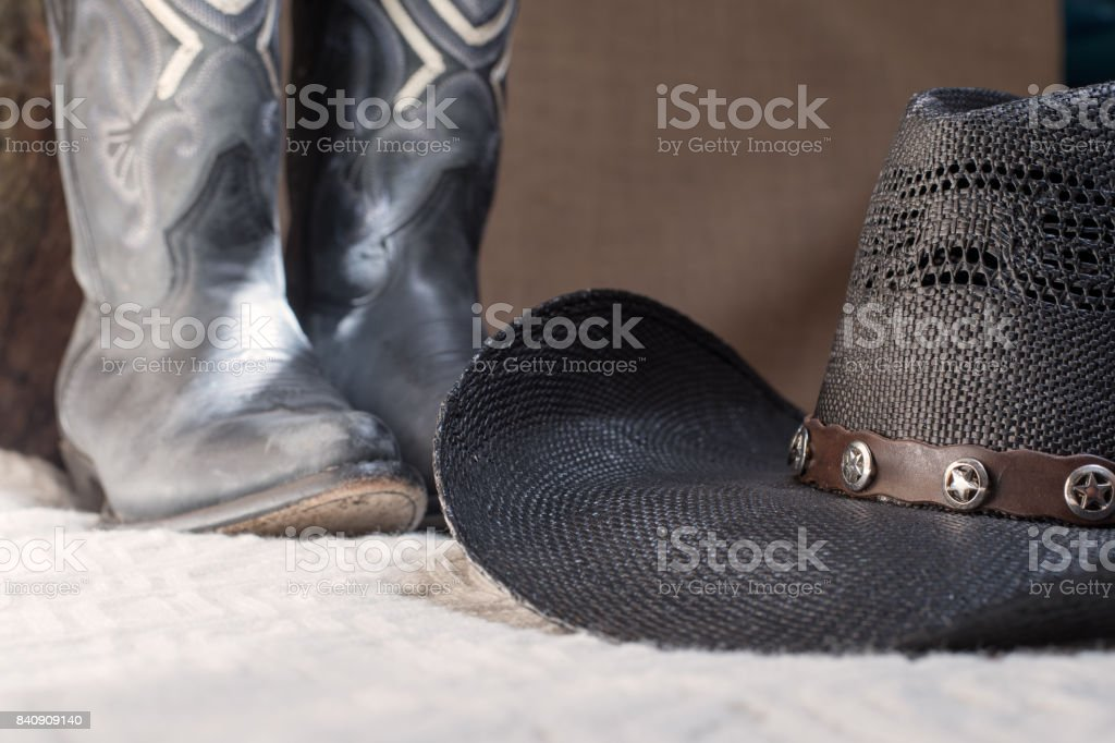 detail of black cowboy hat with blue boots on background