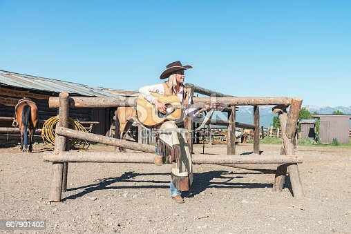 Blonde attractive young woman - cowgirl standing at horse stable singing and playing country guitar. Montana Horseback Riding Ranch, USA.