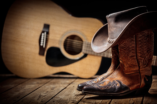 Country music festival live concert with acoustic guitar, cowboy hat and boots background