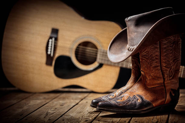 Country music festival live concert with acoustic guitar, cowboy hat and boots stock photo