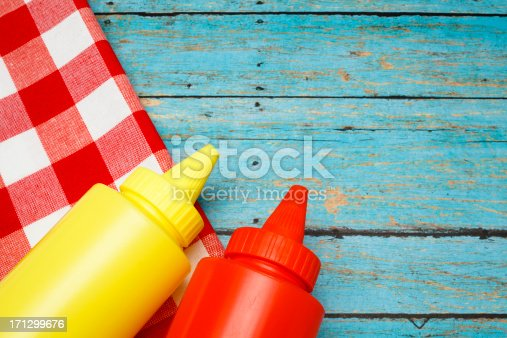 Picnic table with bottles of ketchup and mustard on red checked napkin