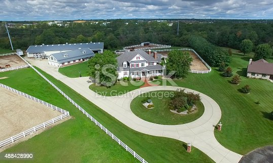 Country ranch, mansion with horse barns and pens.
