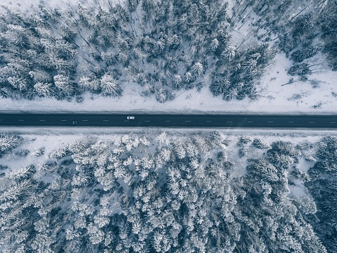 Country road going through the beautiful snow covered landscapes. Aerial view.