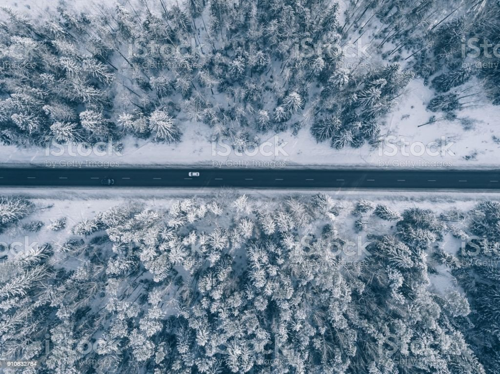 Country road going through the beautiful snow covered landscapes. Aerial view. stock photo