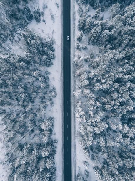 landsvägen går igenom den vackra snön täckte landskap. flygfoto. - pine forest sweden bildbanksfoton och bilder