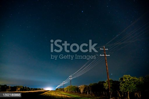 Country Road Illuminated By Traffic in the Night With Stars on Clear Sky