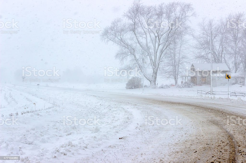 Country Road In A Blizzard With Blowing Snow And Farmhouse stock photo