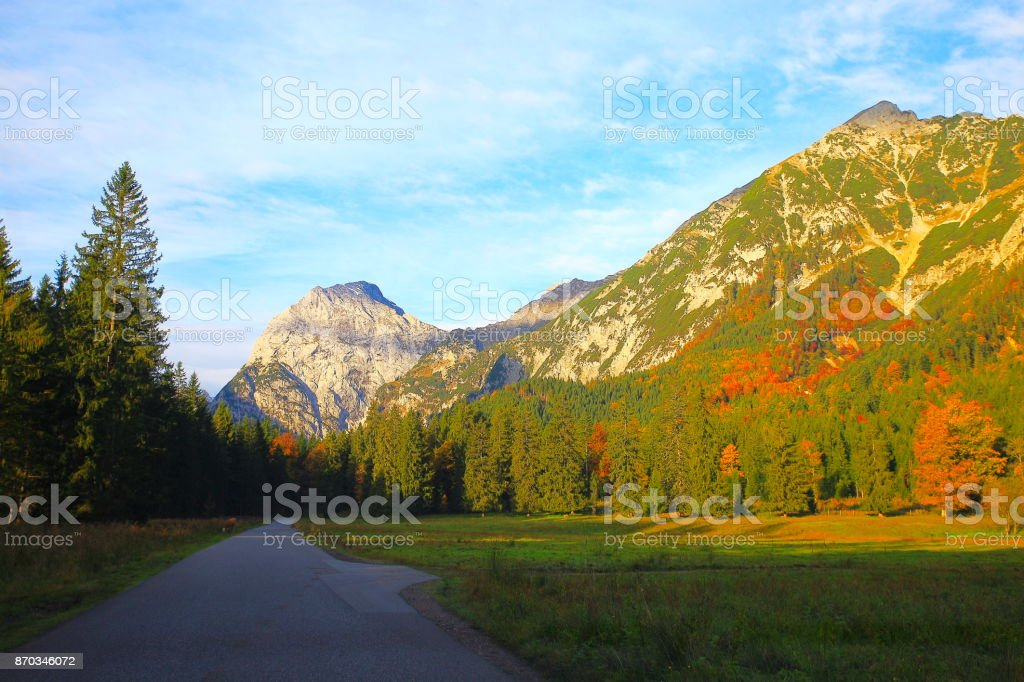 country road - mountain pass to alpine landscape in Austrian Tirol, near Karwendel mountain range and Bavarian alps in Germany - Majestic alpine landscape in gold colored autumn, dramatic Tyrol mountains panorama and Idyllic Tirol meadows, Austria stock photo