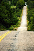 asphalt road straight to deep forest