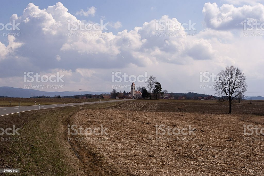 country road straw field tree town white clouds blue sky royalty-free stock photo