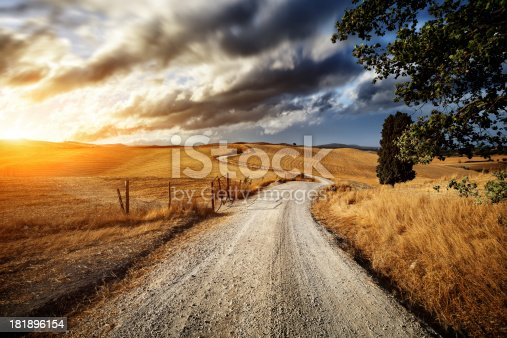 Country road through the golden fields of Tuscany on sunset